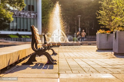 Park Bench with a Water Fountain in the Background
