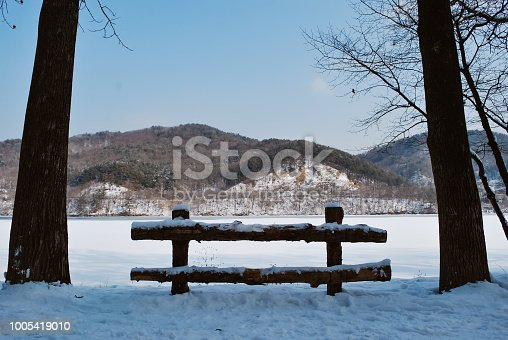 1141614053 istock photo park covered by snow and freezing lake during winter at sunny day 1005419010