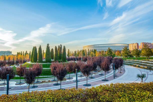 パークガリツコゴ(正式名称パーククラスノダール)。遠くに赤い葉とスタジアムを持つ木。 - クラスノダール市 ストックフォトと画像