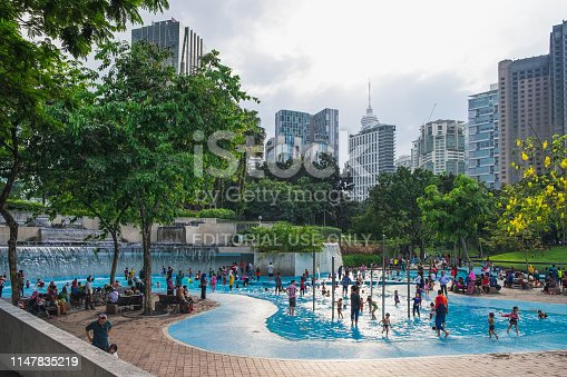 Kuala Lumpur, Malaysia - February 10, 2016: KLCC Park is a public park in Kuala Lumpur, Malaysia. Wading pool is in the middle of the park, in front of Suria KLCC mall and Petronas Twin Towers