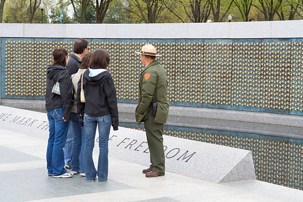 U.S. Park Ranger Explaining World War II Memorial To Tourists Park ranger explaining the meaning of the stars to a family at the World War II memorial in Washington, DC.   - See lightbox for more park ranger stock pictures, royalty-free photos & images