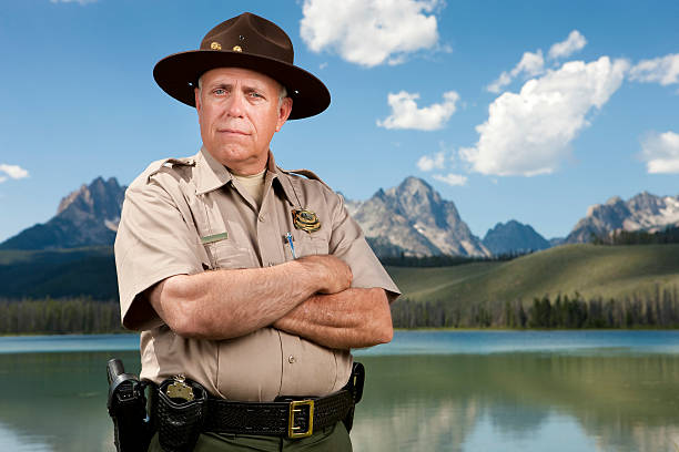 Park Ranger Portrait A mature male park ranger (or police officer) standing in front of a beautiful scenic backdrop of tall mountains and a mirror lake. park ranger stock pictures, royalty-free photos & images