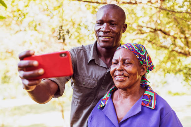 Park Ranger with his Mother Taking a Selfie using Smart Phone stock photo