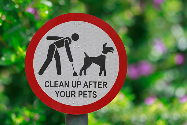 "Park sign in red and white with plants ""Clean up after your pets"" sign at the park poop stock pictures, royalty-free photos & images"