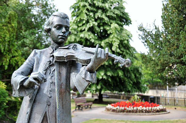 Park Statue Old Bronze Statue in a Public Park of a Young Musician Playing a Violin child prodigy stock pictures, royalty-free photos & images