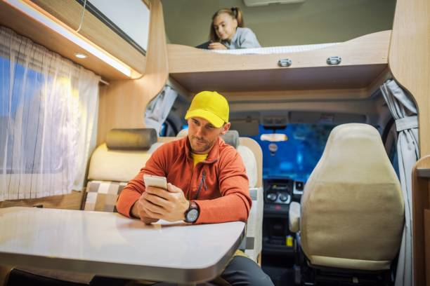 RV Park WiFi Signal Concept Family Spending Time Inside Camper Van RV Motorhome with Their Smartphones. Internet Connection While RVing Concept Photo. Campsite WiFi Signal. rv interior photos stock pictures, royalty-free photos & images