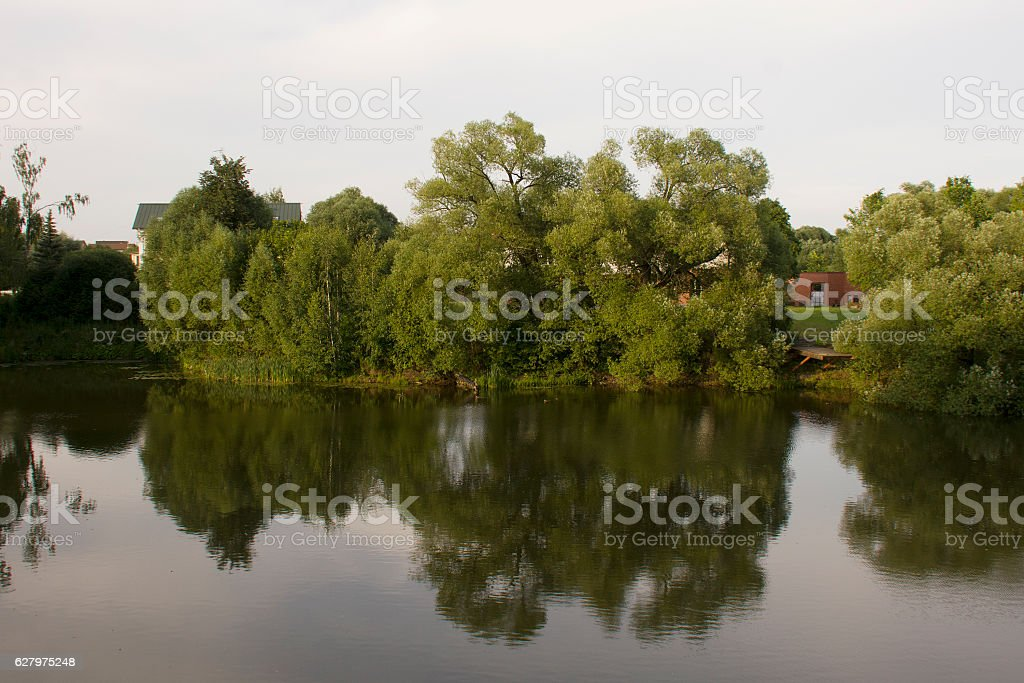 park with buildings, lake and trees stock photo