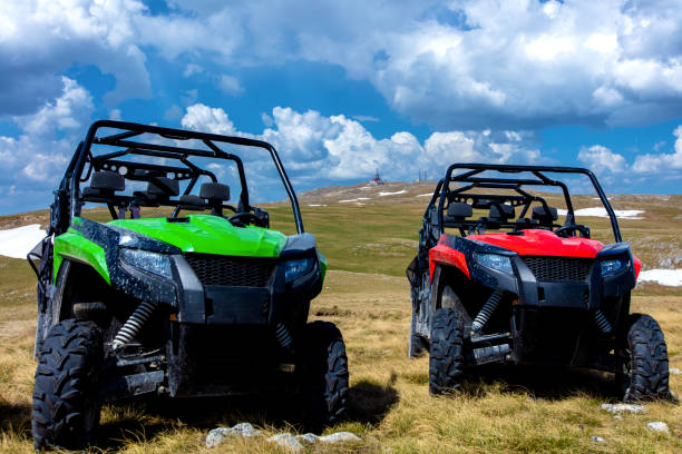 parked atv and utv, buggies on mountain peak with clouds and blue sky in background - bike tire tracks foto e immagini stock