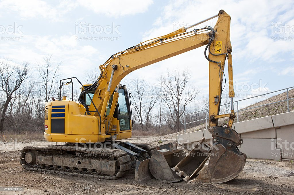 Parked Backhoe At Construction Site stock photo