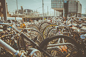 Bicycle handlebars of hundreds of bicycles wheels parked near of Amsterdam Train Station in Holland