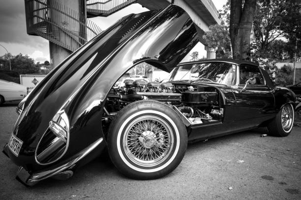 Parked black Jaguar with open Motorhood in Hamburg, Germany Hamburg, Germany - August 8. 2017: Parked black Jaguar with open Motorhood in Hamburg, Germany. Image was developed in black and white. jaguar car stock pictures, royalty-free photos & images