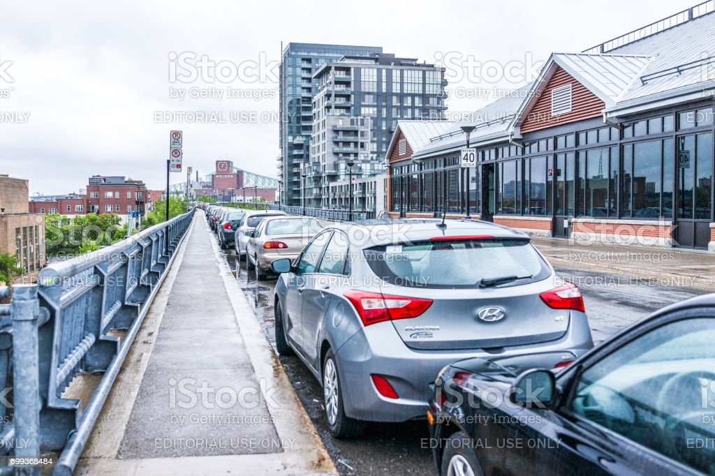 Parked cars on road or street in Quebec region during rainy cloudy wet day stock photo