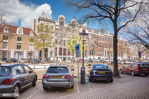 A couple of parked electric cars charge at a charging station along the canals in Amsterdam, Netherlands. One of the cars is a Tesla model s, and the other is a Mercedes c350e. Shot in April 2017.