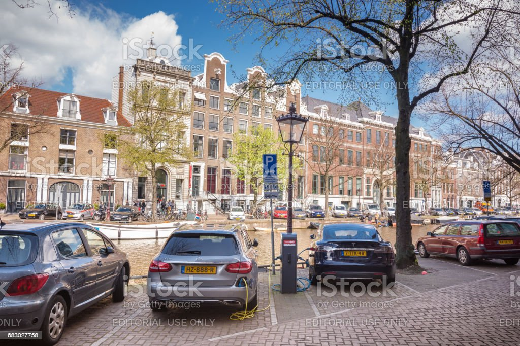 Parked electric cars charging along the canals of Amsterdam, Netherlands stock photo