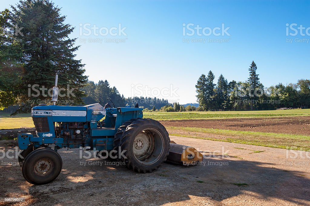 Parked farm tractor in shade after plowing field foto royalty-free