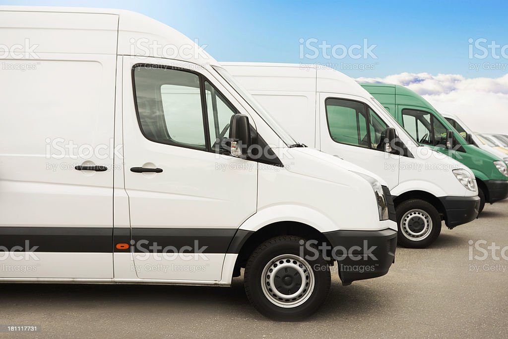 Parked group of white vans / service vehicles after work stock photo