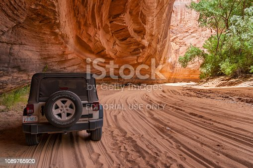 CANYON DE CHELLY, ARIZONA - JUNE 30, 2007: Parked Jeep ATV along sandstone cliffs used by Navajo native guides to drive tourists on the sandy tracks of the Canyon de Chelly, USA.