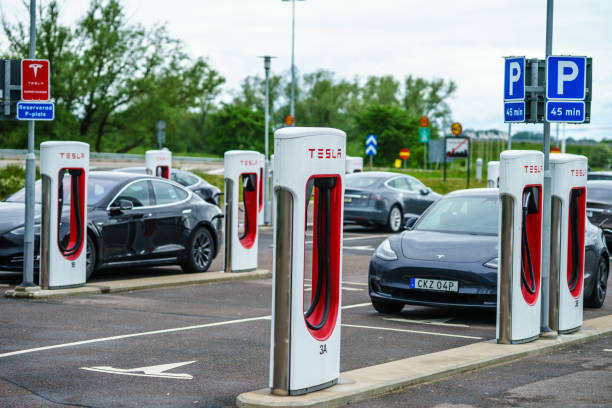 parkerad tesla på laddningspunkt för fulling batteri på laddstationen - elbilar laddning sverige bildbanksfoton och bilder