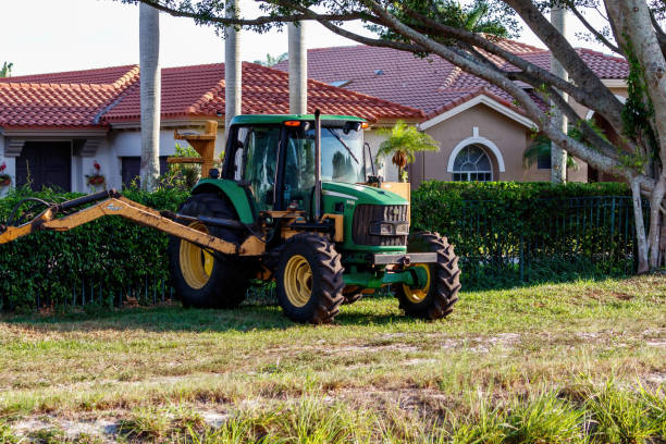 Parked tractor in front of housing neighborhood to clean canal stock photo