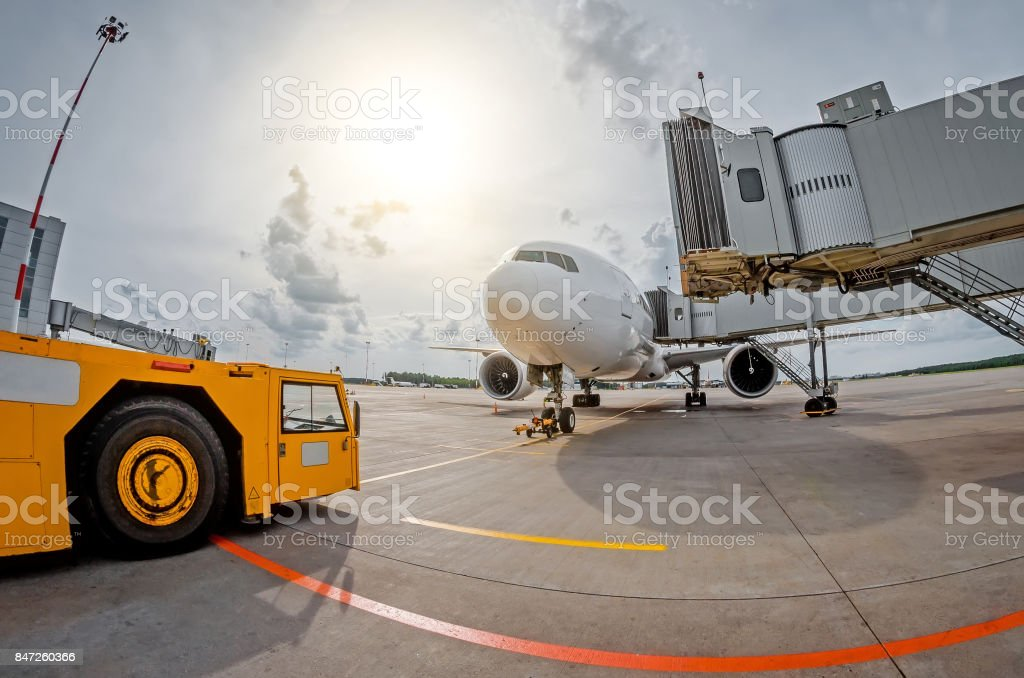 Parking at the airport an airplane at the teletrap and an airfield tractor, ready for departure to the flight stock photo