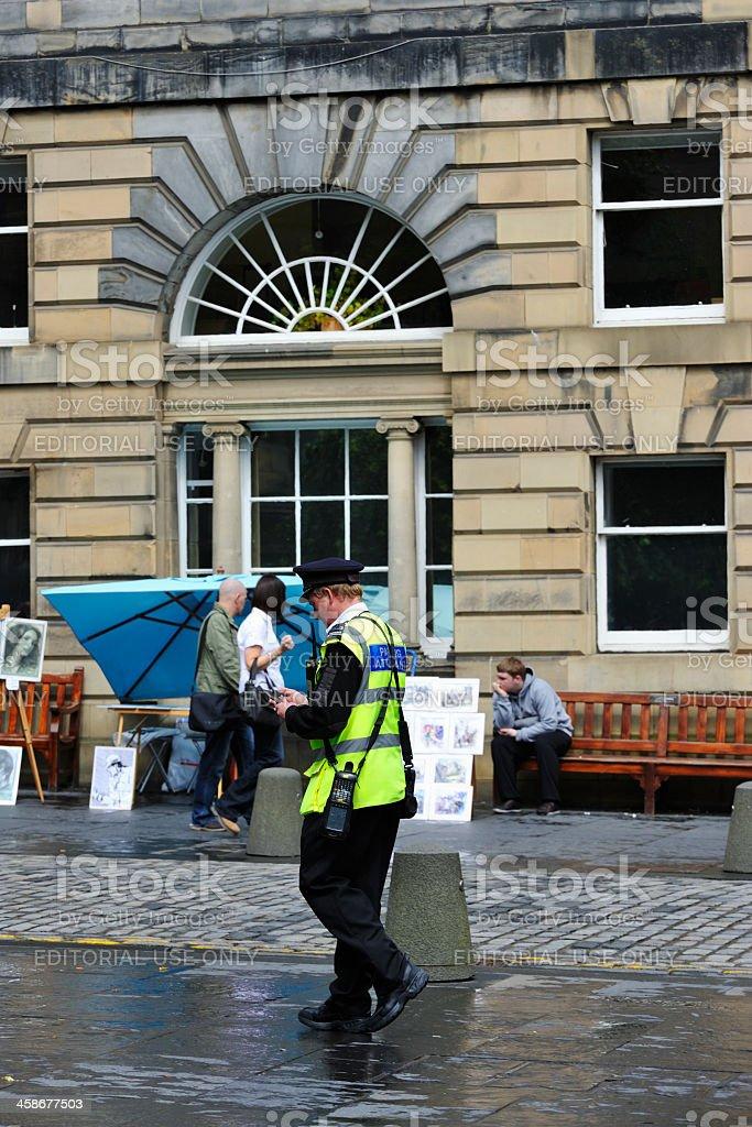 Atendente de estacionamento patrolling uma rua da cidade de Edimburgo - foto de acervo