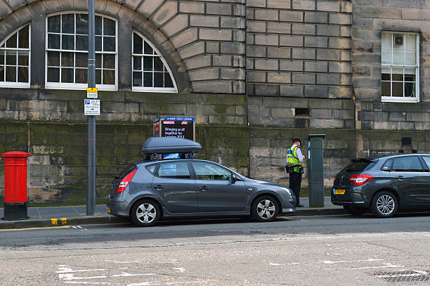 Parking attendant working in Edinburgh Edinburgh, Scotland, UK - July 25, 2012: A parking attendant employed by Edinburgh city council checks a parking ticket machine situated on Chamber Street in the city centre of Edinburgh. johnfscott stock pictures, royalty-free photos & images