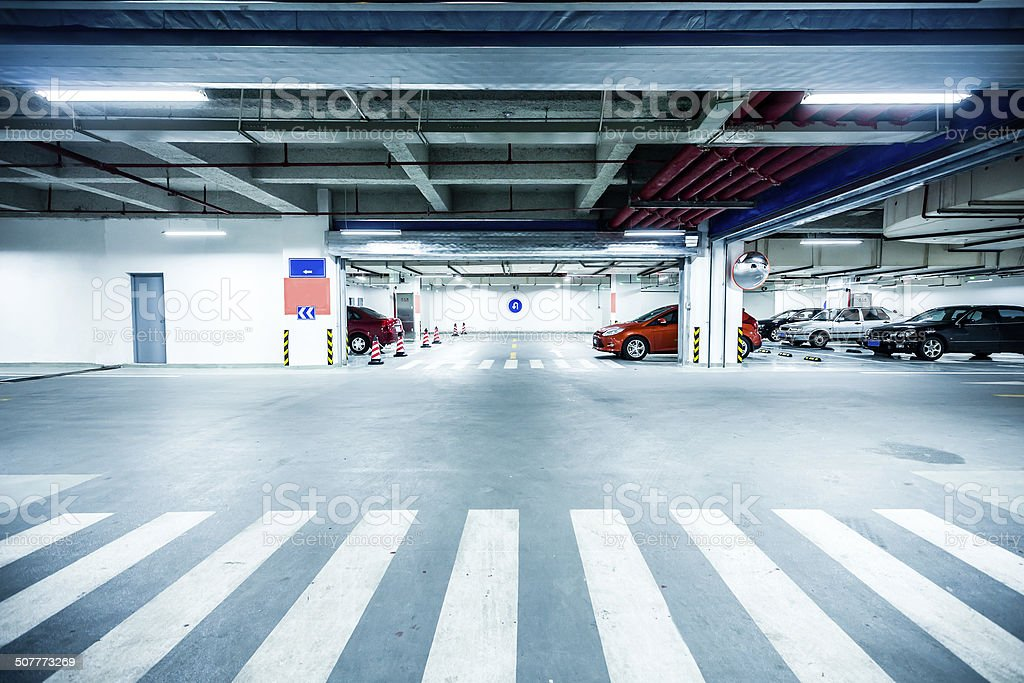 Parking garage, underground interior with a few parked cars stock photo