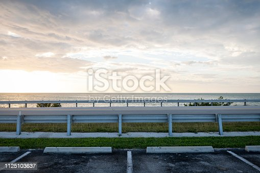 A parking lot at sunrise on Lower Matecumbe Key in the Florida Keys. US 1, called the Overseas Highway in the Florida Keys, is between the guardrails.