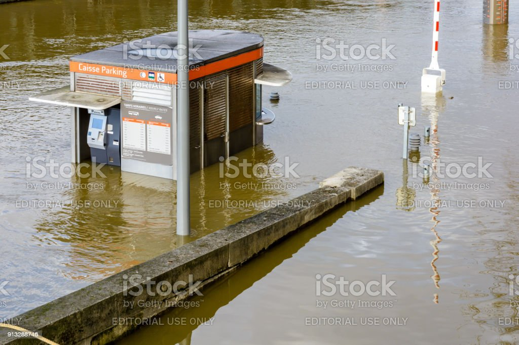 A parking lot toll booth of the 'Bateaux parisiens' tourist shuttle boat company is flooded at mid-height during a winter flooding episode of the Seine in Paris stock photo