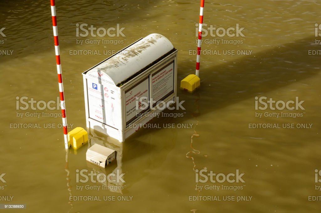 A parking lot toll booth of the 'Vedettes de Paris' tourist shuttle boat company is flooded at mid-height during a winter flooding episode of the Seine in Paris stock photo
