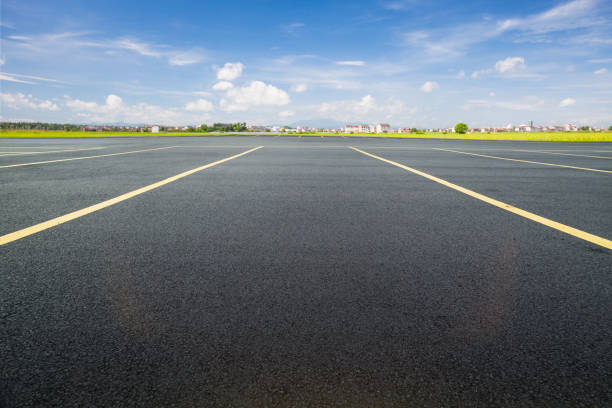 parking lot with black asphalt under blue sky stock photo