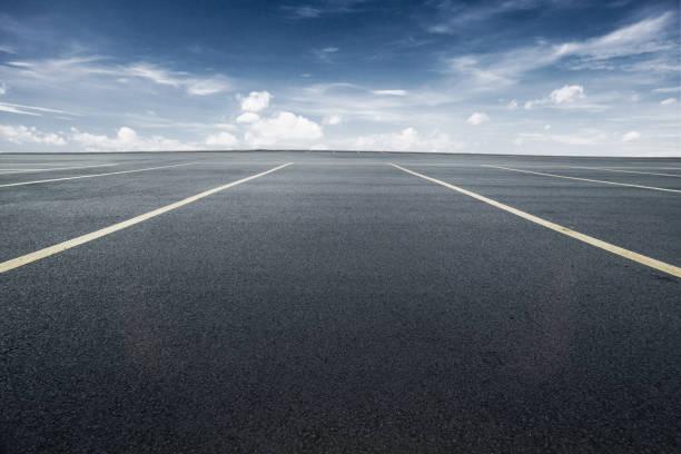 estacionamiento con asfalto negro bajo cielo azul - foto de stock