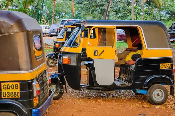 Parking of rickshaws and rickshaw asleep Goa, India - November 16, 2012: Parking of auto rickshaws. A tuk-tuk driver is taking a nap lying inside the car. three wheel motorcycle stock pictures, royalty-free photos & images