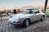 Hamburg, Germany - August 8. 2017: A silvergray Porsche 911, parks on Hamburg Fischmarkt during the event with Magnus Walker. The harbor cranes can be seen in the background.