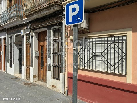 Valencia, Spain - May 24, 2020: Pole with parking sign for handicapped people in the sidewalk. This places can be asked for by people with disabilities to the city government when they live in front of them