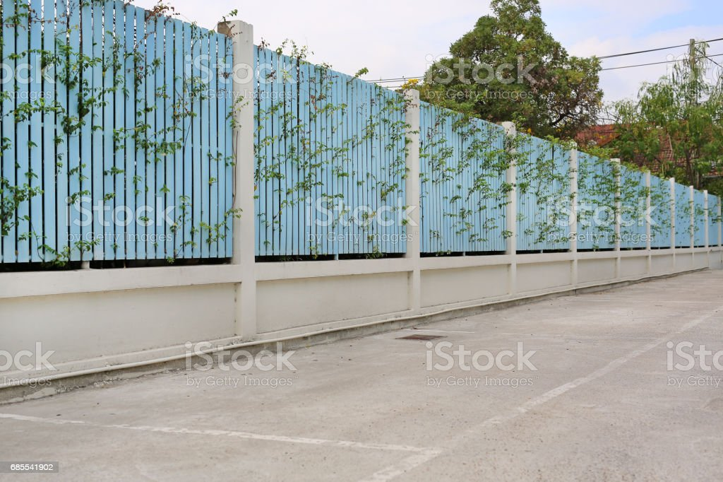 Parking spaces by a wood plank wall along an empty road. 免版稅 stock photo