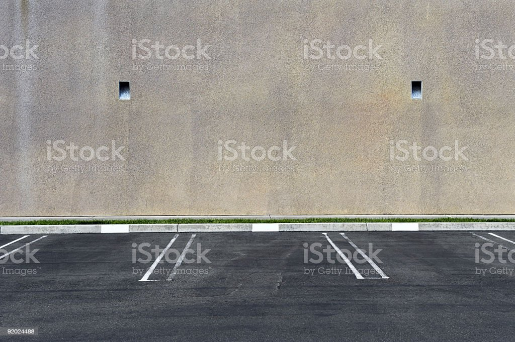 Parking spots against a blank wall stock photo