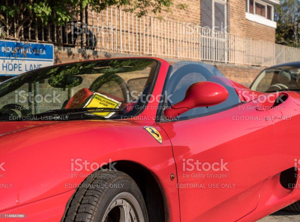 Yellow parking violation notice on red Ferrari sports car