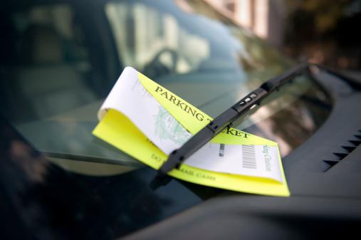 A parking ticket under the wiper blade awaits a future unhappy motorist.