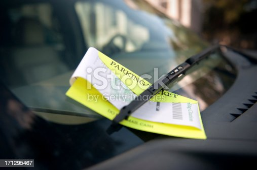 A parking ticket under the wiper blade awaits a future unhappy motorist.