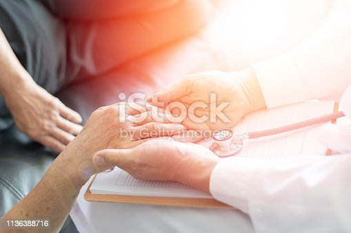 istock Parkinson and alzheimer female senior elderly patient with caregiver in hospice care. Old woman holding hand with doctor physician. 1136388716