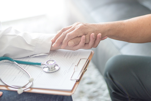 istock Parkinson and alzheimer female senior elderly patient with caregiver in hospice care. Old woman holding hand with doctor physician. 1136388719