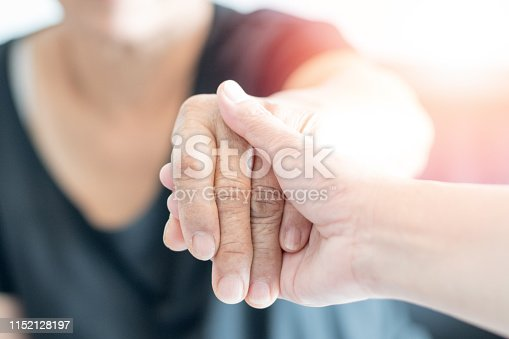 istock Parkinson and Alzheimer female senior elderly patient with caregiver in hospice care. Doctor hand with stethoscope check up older woman people. Old aging person seeing medical physician in hospital. 1152128197