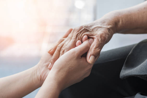 Parkinson disease patient, Alzheimer elderly senior, Arthritis person hand in support of nursing family caregiver care for disability awareness day, National care givers month, ageing society concept stock photo