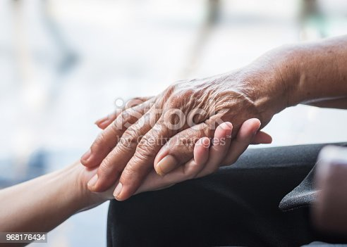 istock Parkinson disease patient, elderly senior person in support of nursing family caregiver for disability awareness day concept 968176434