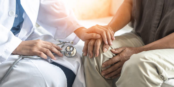 Parkinson's disease patient, Arthritis hand and knee pain or mental health care concept with geriatric doctor consulting examining elderly senior aged adult in medical exam clinic or hospital stock photo