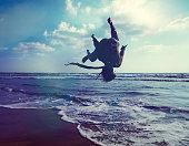 istock Parkour muscular athlete doing backflip jump on the beach 874095970