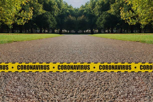 parksperrkonzept: ein leerer park, der nach dem schließen von einem gelben und schwarzen sicherheitsband mit dem wort coronavirus umgeben ist, um eine ansteckung zu verhindern. - standbildaufnahme stock-fotos und bilder