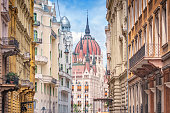 Stock photograph of the Parliament building and old, ornate apartment buildings in Budapest, Hungary on a sunny day.