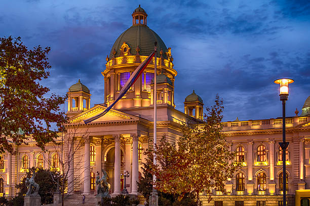 parliament of the republic of serbia in belgrade at night - belgrade serbia stock photos and pictures